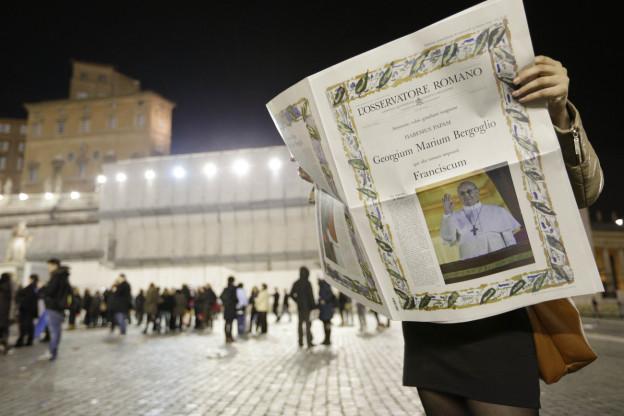 Frau hält Zeitung mit Papst auf der Titelseite in den Händen.