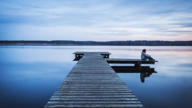 Ein Steg auf einem See, darauf sitzt eine Frau und blickt in die Ferne.