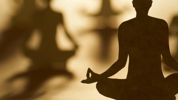 Schatten von meditierenden Menschen.
