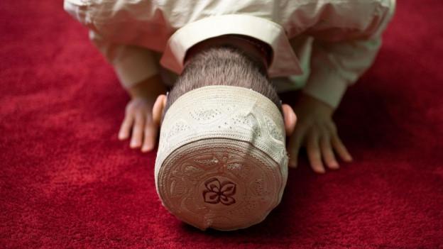 Ein Muslime kniet auf einem roten Teppich und berührt mit seinem Kopf den Boden.