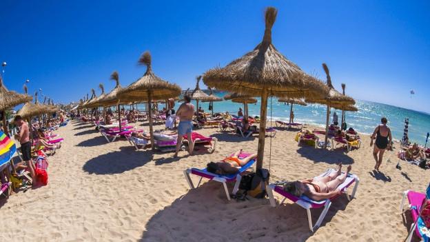 Strand mit Sonnenstühlen, Touristen in Badenazügen und Strohsonnenschirme