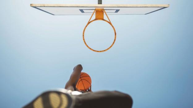 Ein Basketballspieler, der den Ball in den Korb wirft.