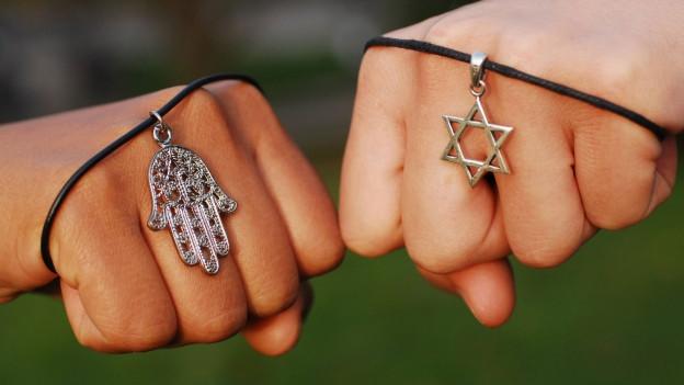 Zwei Fäuste mit je einem religiösen Amulette