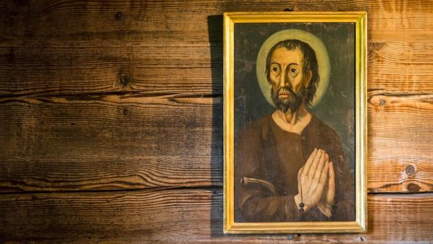 Bruder Klaus Bild an einer Holzwand.