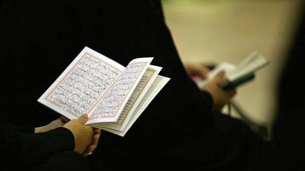 Frau hält Koran in den Händen