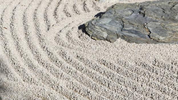 Symmetrische Linien im Kies umrunden grosse Steine