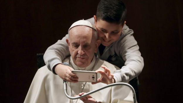 Der Papst macht ein Selfie mit einem Jungen