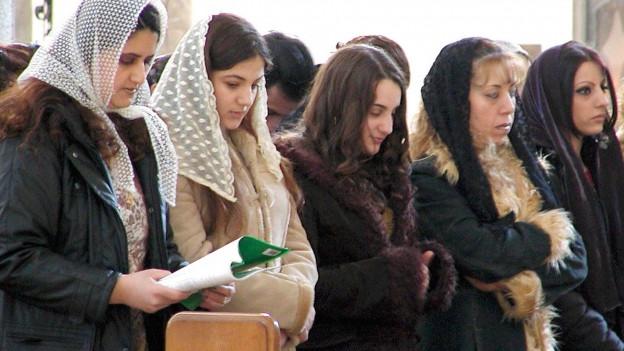 Frauen stehen in einer Kirchbank und schauen in einen Text