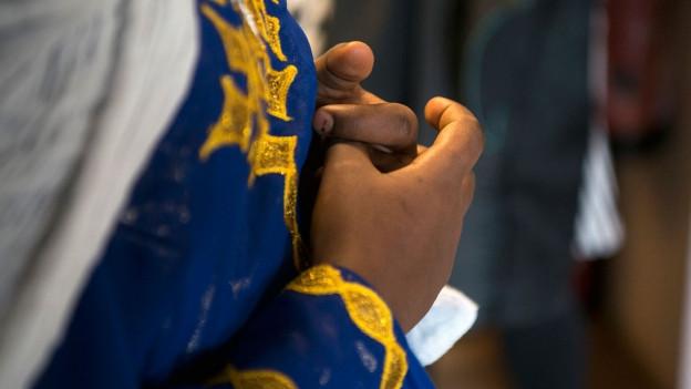 Ein eritreisches Mädchen in einer Flüchtlingsunterkunft faltet die Hände.