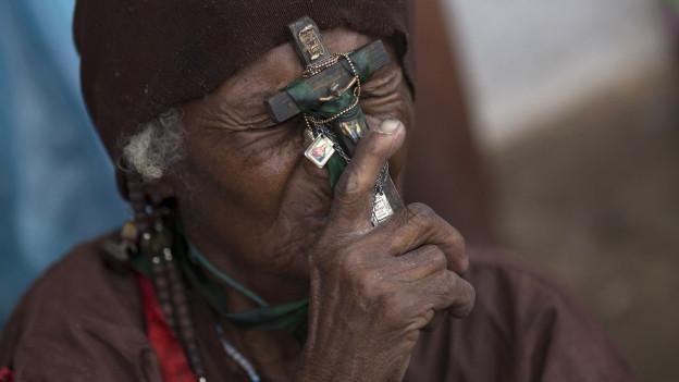 Ein Brasilianer hält einen Kruzifix.
