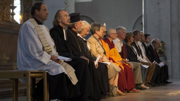 Vertreter von Islam, katholischer und orthodoxer Kirche, Buddhismus, Judentum und Islam stzen gemeinsam auf einer Kirchenbank