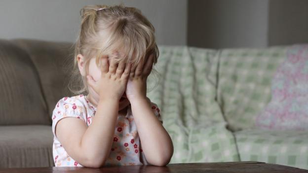 Kleines Mädchen versteckt sein Gesicht hinter den Händen
