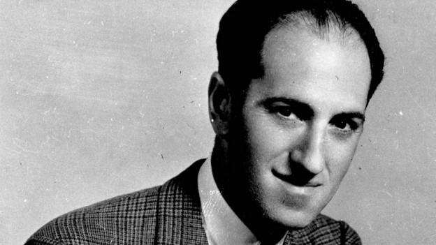Eine alte schwarz-weiss Aufnahme von Georg Gershwin vor einem Fenster, den Blick zur Seite gerichtet.