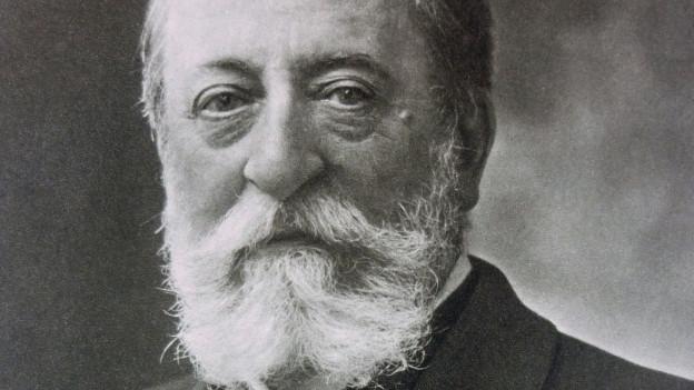 Schwarz-Weiss-Porträt eines älteren Herrn mit kurzem, weissem Haar.