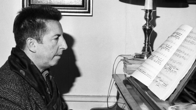 Schwarzweissfoto: Ein Mann spielt Klavier.