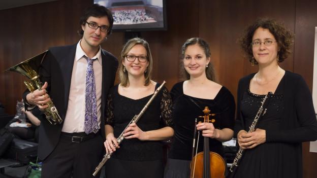 Ein Mann und drei Frauen stehen nebeneinander. Alle sind adrett gekleidet und halten Instrumente in der Hand.