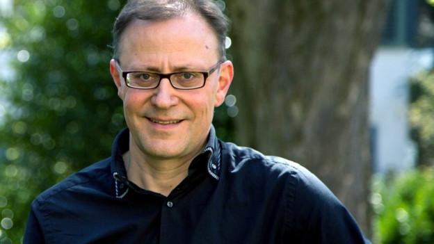 Ein Mann mit Brille steht vor einem Baum und lacht.
