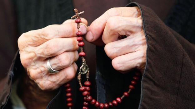 Eine alte Person hält eine Rosenkranz in den Händen.