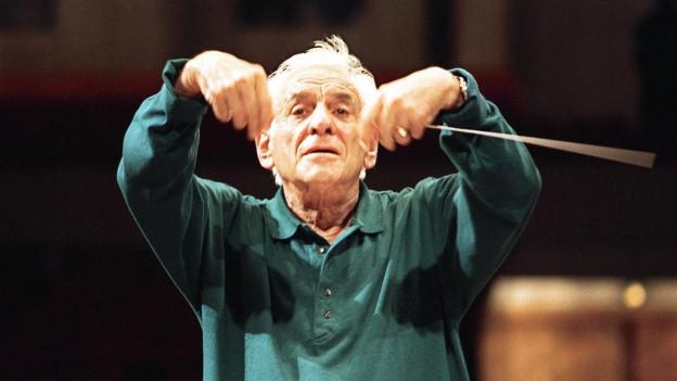 Foto von Leonard Bernstein während dem er dirigiert.