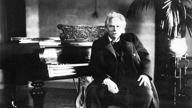 Schwarzweiss Foto von einem älteren Herr, der vor einem Flügel sitzt.