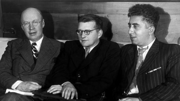 Dimitri Schostakowitsch sitzt zwischen zwei anderen Männern auf dem Sofa