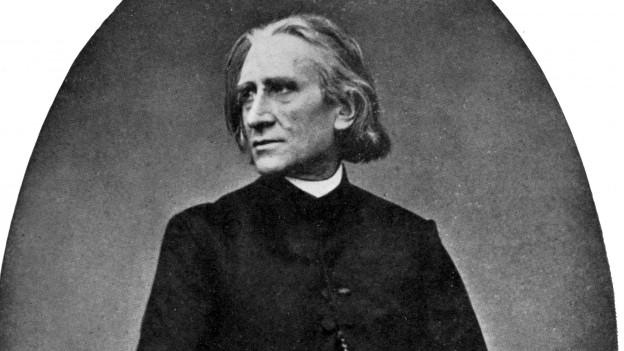 Ein Herr in langem schwarzen Mantel und kinnlangen Haaren