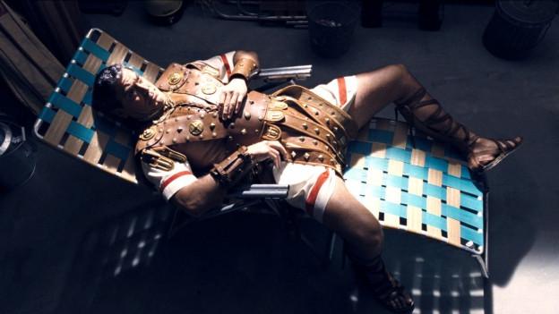 Ein Mann in römischer Bekleidung sitzt auf einem Liegestuhl.