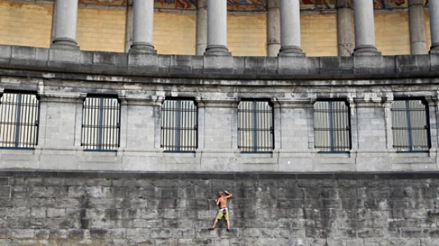 Ein Mann übt sich im Klettern an der Mauer des Cinquantenaire Monuments in Brüssel.