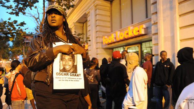 Frau in Demonstrationszug hält Bild von Oscar Grant in der Hand.