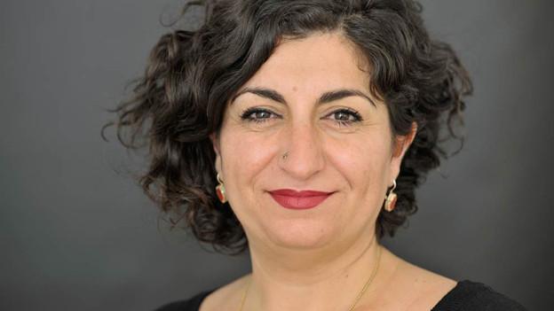 Die Fotografie zeigt eine Frau mittleren Alters mit schwarzen Locken, roten Lippen und lächelnd.