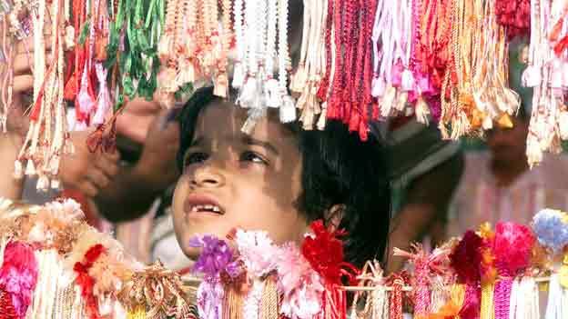 Die Fotografie zeigt ein junges indisches Mädchen, das zwischen einem Vorhang aus bunten Bändern hindurch blickt.