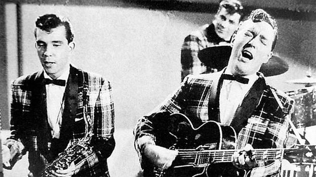 «Rock Around the Clock»-Sänger Bill Haley (r.) während eines Fernsehauftrittes, 1954