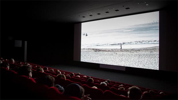 dunkler Kinosaal, auf der Leinwand ist ein Strand zu sehen