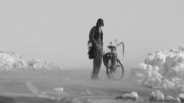 Filmszene, schwarzweiss: Ein Mann dteht neben einem Fahrrad in einer kargen Landschaft