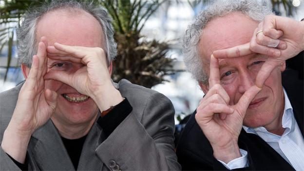 Die beiden Brüder schauen in die Kamera. Beid ebilden mit ihren Händen einen Rahmen, durch den sie blicken.