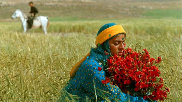 Filmszene: In einem Feld sitzt eine junge Frau in bunter Tracht und hält einen grossen Blumenstrauss. Im Hintergrund sitzt ein Mann auf einem Pferd.