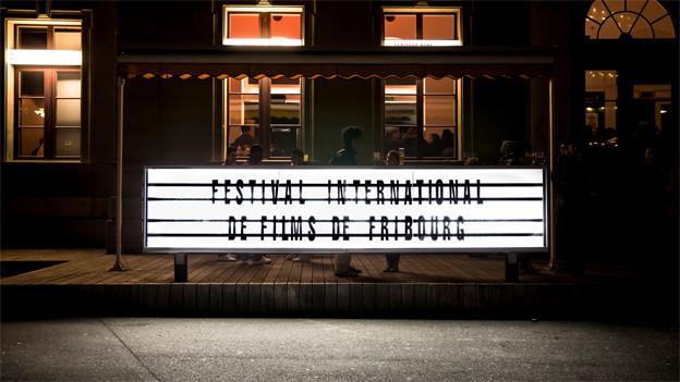 """NAcht, ein beleuchtetes Gebäude. Davor ein leuchtendes Schild mit der Aufschrift """"Festval International de Films de Fribourg"""""""
