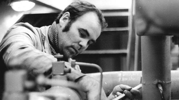 Die schwarz-weisse Fotografie zeigt einen Mann bei der Arbeit an einem Rohr.
