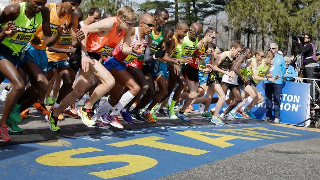 Marathonläufer beim Start, am Boden ist der Schriftzug Start in gelb auf blauem Grund erkennbar.