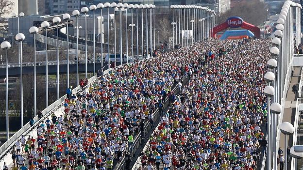 Eine Brücke mit hohen Lampen auf der Seite bevölkert von einer Masse von Marathonläufern.