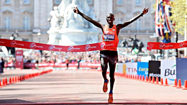 Marathonläufer beim Zieleinlauf, die Arme hoch jubelnd hochgestreckt.