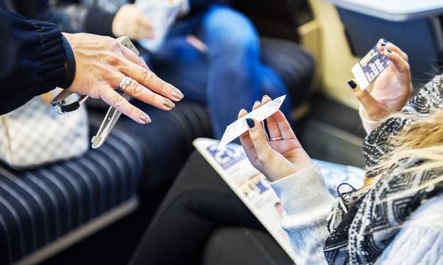 Die Nahaufnahme von zwei Händen, die ihren Fahrausweis im Zug der Kontrolleurin zeigen.