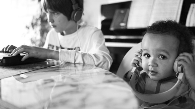 Zwei Kinder hören sich über Kopfhörer Musik an.