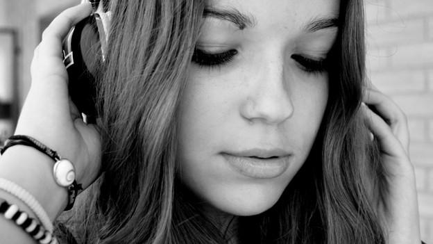 Ein Mädchen hört Musik über Kopfhörer.