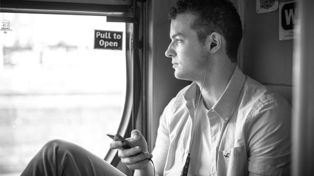 Ein Mann schaut nachdenklich aus dem Fenster eines Zuges und hört über Kopfhörer Musik.