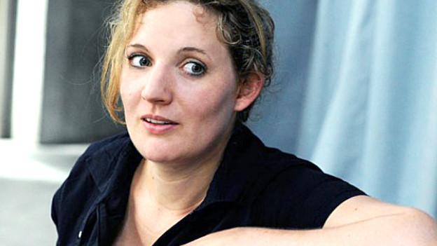 Eine junge Frau mit hellen Haaren schaut in die Kamera.