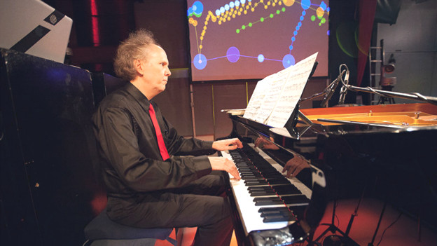 Ein Mann spielt Klavier in einem Club.