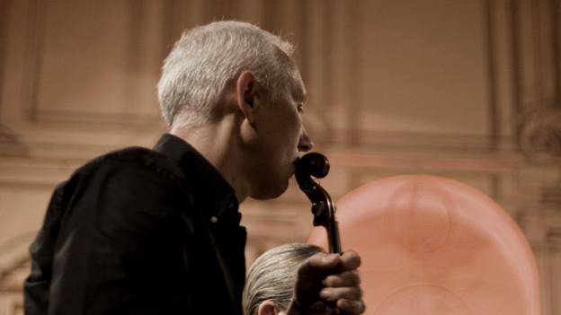 Ein weisshaariger jüngerer Mann mit Geige