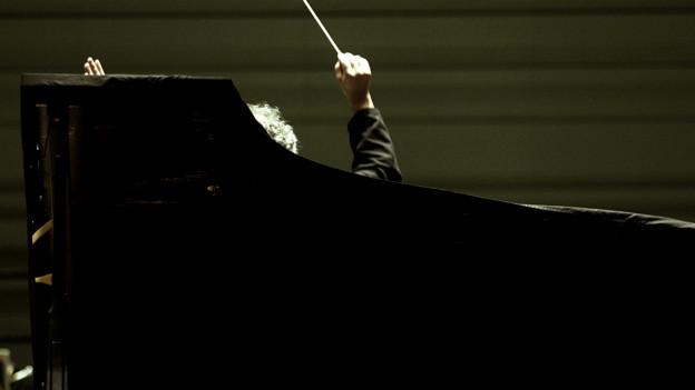 Hinter einem aufgeklappten Flügel sieht man Schopf und Arm eines Dirigenten.