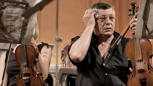 Ein Orchestergeiger tupft sich mit verzweifeltem Gesicht die Stirn ab.